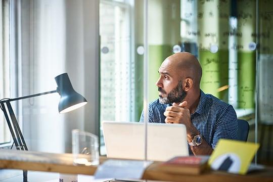 Man Thinking Behind Desk